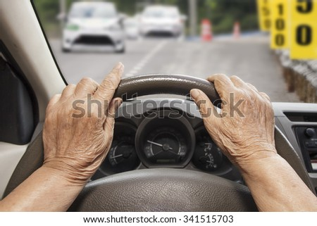 Senior woman driving a car on construction road. - stock photo