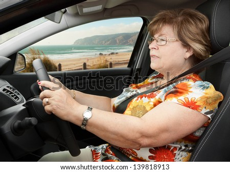 Senior Woman Driving a Car Through the Beach Road - stock photo