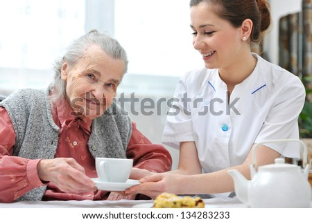 Senior woman eats lunch at retirement home - stock photo