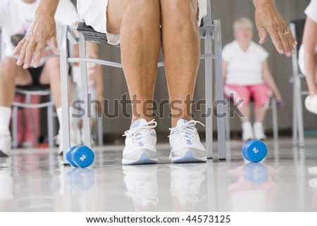 Senior woman exercising in a gym - stock photo