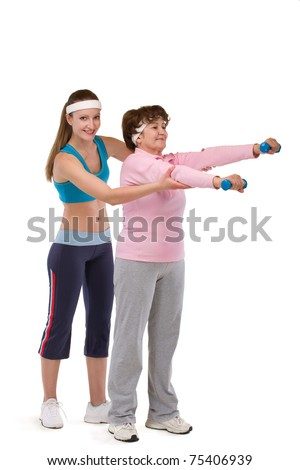 senior woman exercising in gym with young instructor - stock photo
