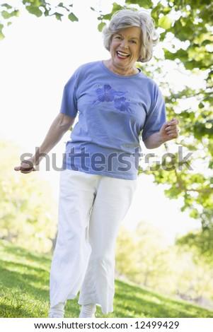 Senior woman exercising in leafy park - stock photo