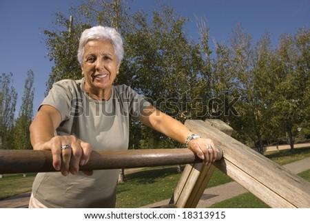 Senior woman exercising in the park - stock photo