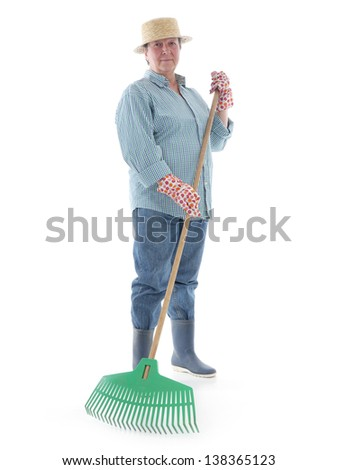 Senior woman gardener wearing straw hat and rubber boots posing with plastic lawn rake over white background - stock photo
