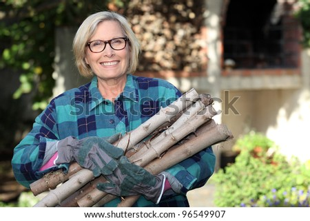 senior woman gathering wood in the garden - stock photo