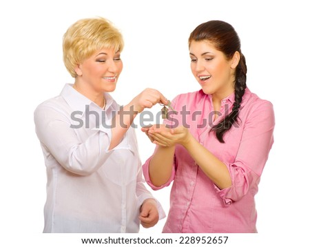 Senior woman give keys to young woman isolated - stock photo