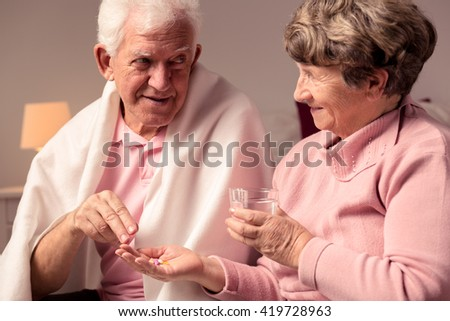 Senior woman giving medicines to her ill husband - stock photo