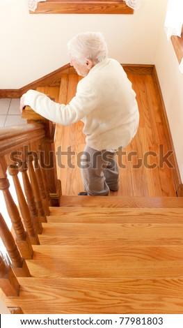 Senior Woman going down staircase - stock photo