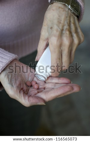 Senior woman hands Close up of senior woman's hands taking her medicines - stock photo