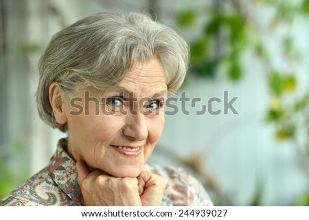 Senior woman happy at home on green background - stock photo