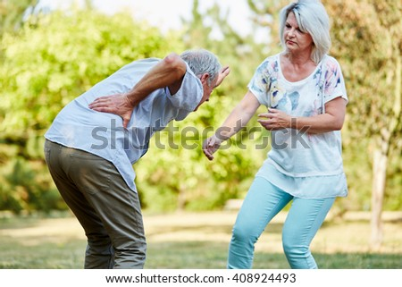 Senior woman helps man having lumbago pain in the park in summer - stock photo
