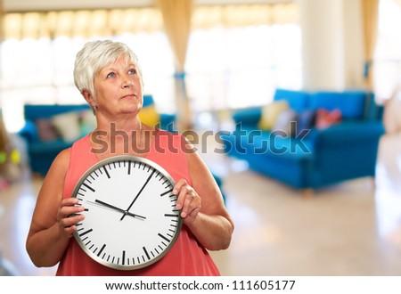Senior Woman Holding A Clock, Indoor - stock photo
