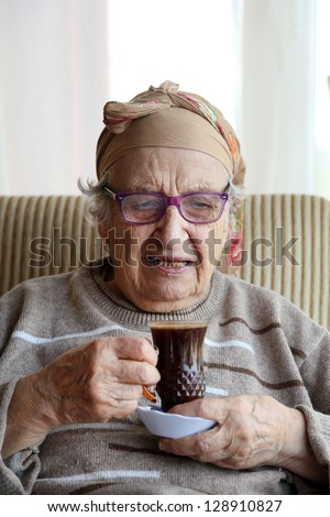 senior woman holding a glass of coffee - stock photo