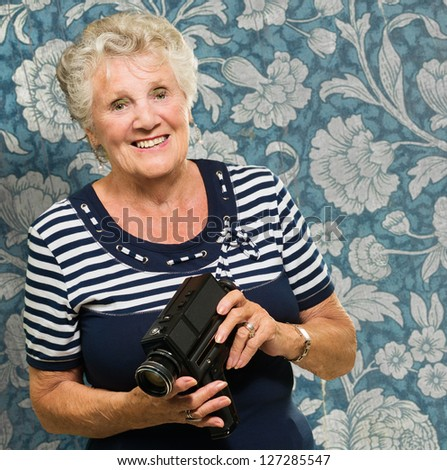 Senior Woman Holding Camera Isolated Against Wallpaper - stock photo