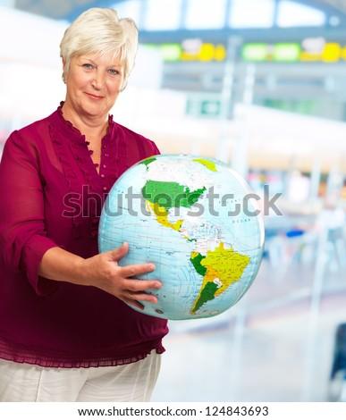 Senior Woman Holding Globe, Indoors - stock photo