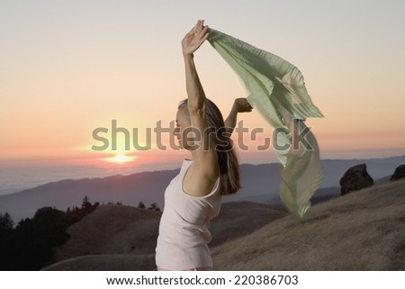 Senior woman holding her sweater into the wind - stock photo