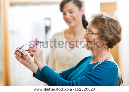 Senior woman holding new glasses with salesgirl in background at store - stock photo
