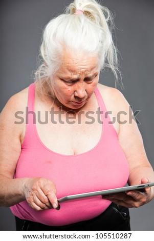 Senior woman holding tablet long grey hair. Studio shot. Isolated on grey background. - stock photo