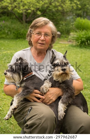 Senior woman hugs her two pets, black and silver miniature schnauzer dog in countryside - stock photo
