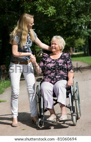 Senior woman in a wheelchair and her granddaugther - stock photo