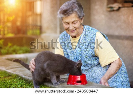 Senior woman in apron with her gray cat outside her house. - stock photo