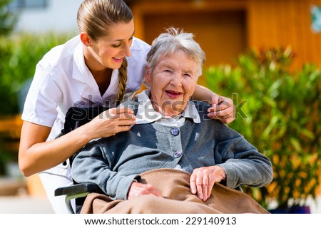 Senior woman in nursing home with nurse in garden sitting in wheelchair  - stock photo