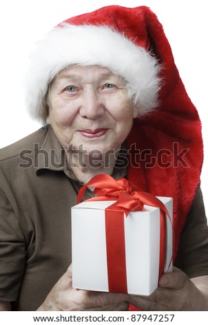 Senior woman in Santa hat with gift - stock photo