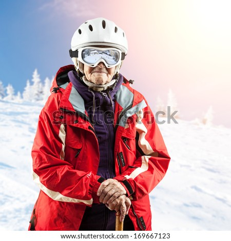 Senior woman in ski jacket and goggles outdoors. With path. - stock photo