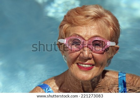 Senior woman in swimming pool - stock photo