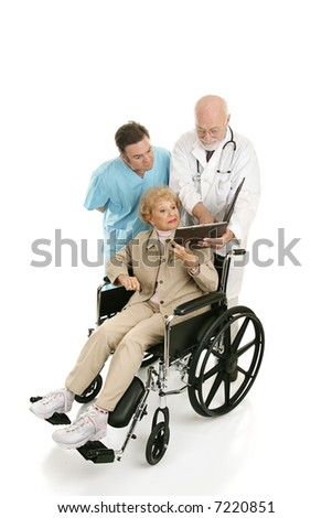 Senior woman in wheelchair discussing her chart with her doctors.  Full body isolated on white - stock photo