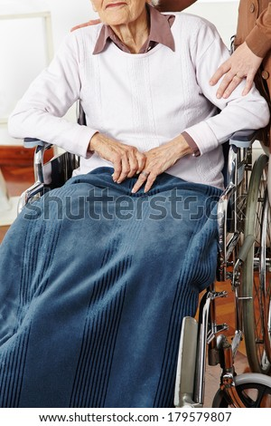 Senior woman in wheelchair getting help from caregiver - stock photo