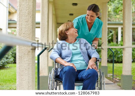 Senior woman in wheelchair talking to a nurse in a hospital garden - stock photo