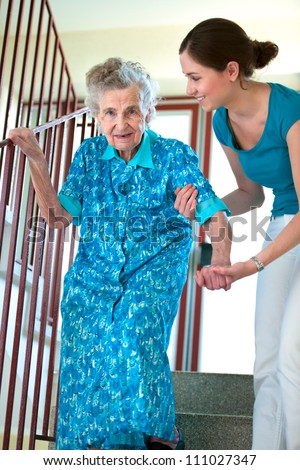 Senior woman is climbing stairs with caregiver - stock photo