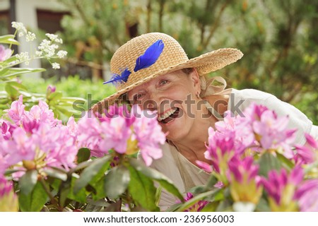 Senior woman laughing behind rhododendron flowers. She's wearing a straw hat with a blue feather in it. - stock photo