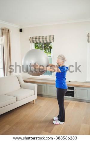 Senior woman lifting exercise ball while exercising at home - stock photo