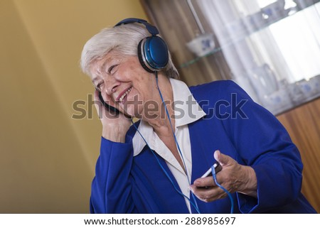 Senior woman listening music at home. - stock photo
