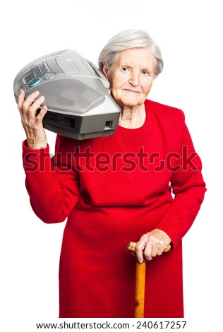 Senior woman listening to music while carrying stereo recorder over white - stock photo