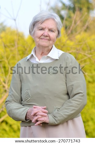 Senior woman looking and smiling in garden on blue sky. - stock photo