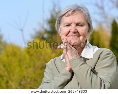 Senior woman looking and smiling in garden on blue sky. MANY OTHER PHOTOS FROM THIS SERIES IN MY PORTFOLIO.  - stock photo