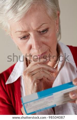 Senior woman looking at prescription drug pack - stock photo