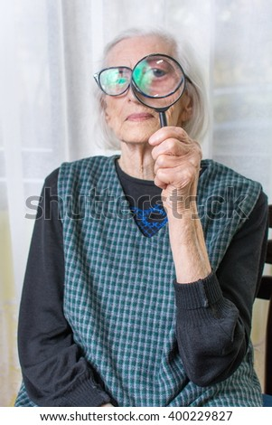 Senior woman looking through magnifying glass indoors - stock photo