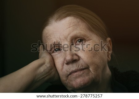 senior woman looking to the camera with sad look shalow DOF - stock photo