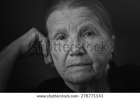 senior woman looking to the camera with shalow DOF - stock photo