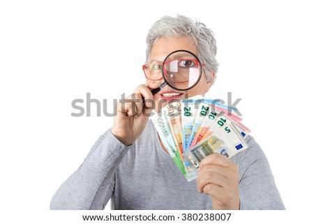 Senior woman looks through a magnifying glass on euro money - stock photo