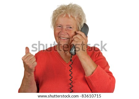 Senior woman makes OK gesture with a telephone - stock photo