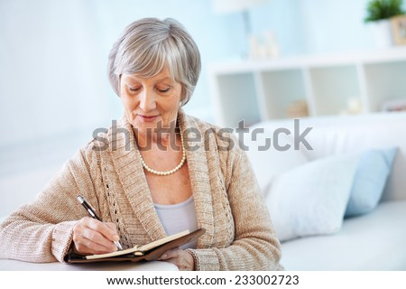 Senior woman making notes in notepad - stock photo