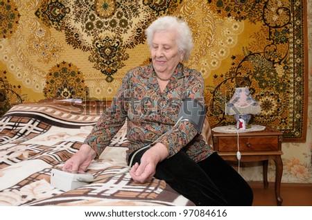 Senior woman measures her blood pressure in bedroom - stock photo