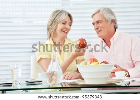 Senior woman offering her husband a red apple - stock photo