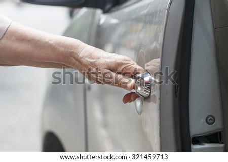 senior woman open car door  - stock photo