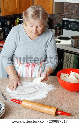 Senior woman or grandma making pie in her home kitchen - stock photo